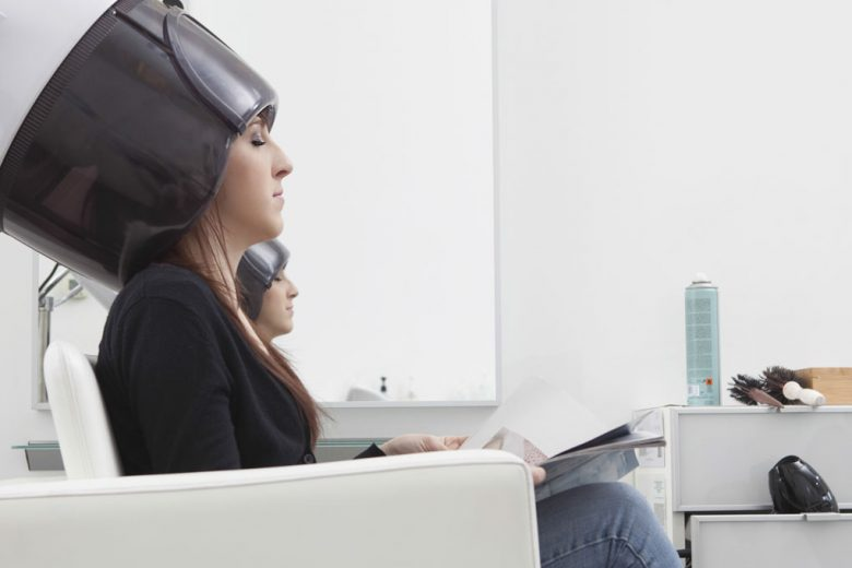 Lady having hair dried at a salon, using a white bonnet hood hair dryer
